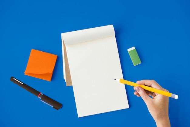 La vista aérea de la mano que sostiene el lápiz escribe la libreta en la tabla azul