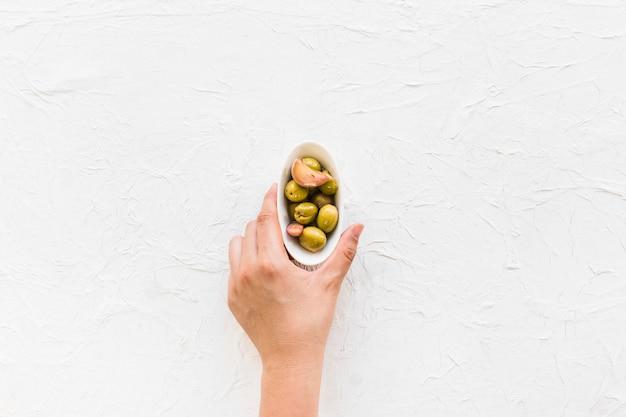 Vista aérea de la mano que sostiene el tazón de aceitunas con dos dientes de ajo