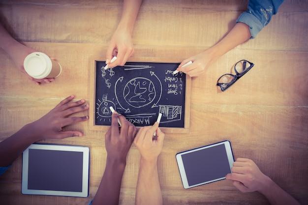 Vista aérea de manos recortadas escribir términos comerciales en la pizarra con la persona que toca la tableta digital