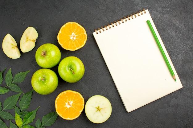 Vista aérea de manzanas verdes frescas enteras y picadas y naranjas de menta cortadas junto al cuaderno con lápiz sobre fondo negro