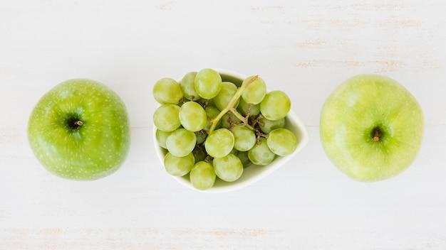 Una vista aérea de manzanas verdes con uvas sobre fondo blanco con textura de madera
