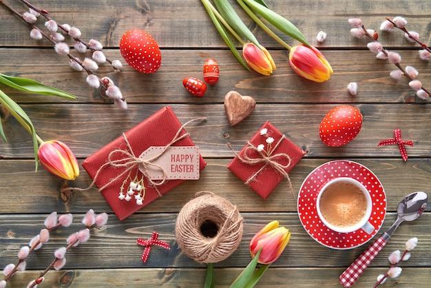 Vista aérea de la mesa de madera con decoraciones de primavera, taza de café, regalos envueltos, flores y huevos de pascua