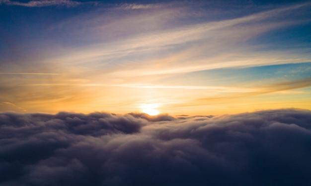 Vista aérea místicas nubes grises de invierno amontonadas con el telón de fondo de una puesta de sol dorada en el invierno