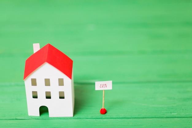 Una vista aérea del modelo de casa en miniatura cerca de la etiqueta de venta en el fondo con textura verde