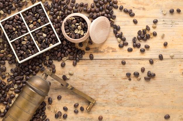 Una vista aérea de un molinillo de café viejo con granos de café en un recipiente y una mesa