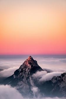 Vista aérea de una montaña cubierta de niebla bajo el hermoso cielo rosado