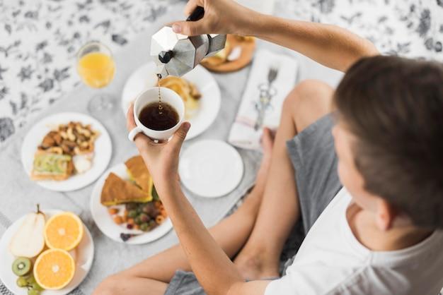 Una vista aérea de un muchacho que vierte té en taza con el desayuno en la tabla