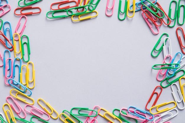 Vista aérea de muchos clips de papel coloridos formando marco