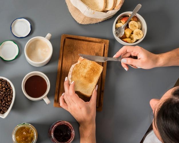 Una vista aérea de la mujer aplicando mermelada en el pan con un cuchillo de mantequilla sobre fondo gris
