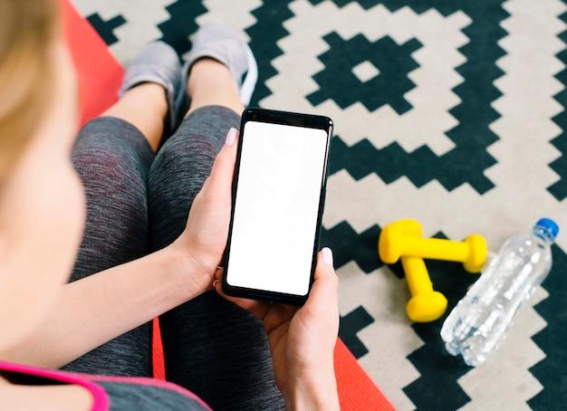 Una vista aérea de la mujer joven en forma que sostiene el teléfono móvil que muestra la pantalla en blanco en blanco