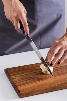 Una vista aérea de una mujer joven que corta el cuchillo con la seta en la tabla de cortar de madera