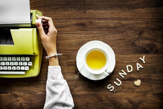 Vista aérea de una mujer con una máquina de escribir retro y el concepto de ocio de domingo de la palabra
