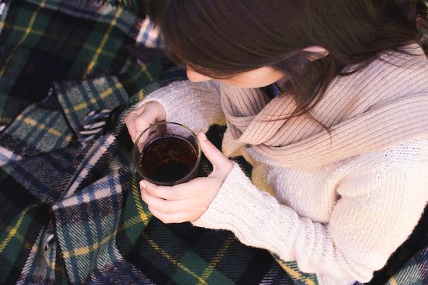 Una vista aérea de una mujer sosteniendo una taza de té de hierbas en la mano
