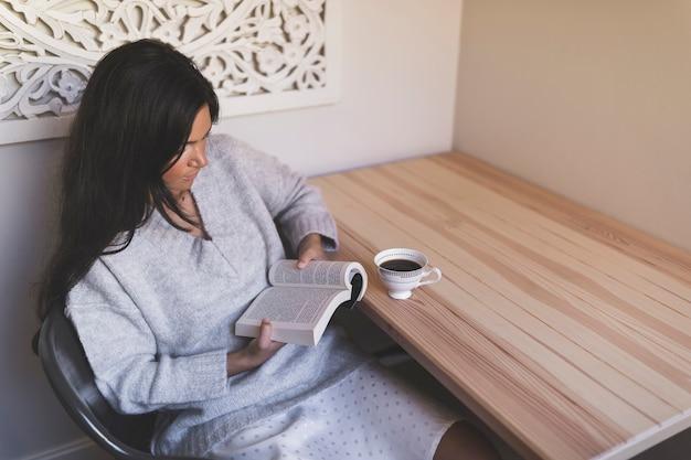 Una vista aérea de una niña leyendo un libro con una taza de café en la mesa