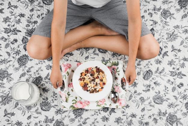 Una vista aérea de un niño sentado en la alfombra floral con bandeja de copos de avena