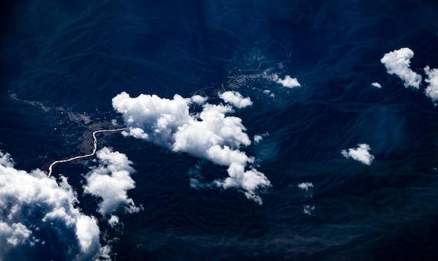 Vista aérea de la nube y el cielo desde la ventana del avión mirando hacia la tierra