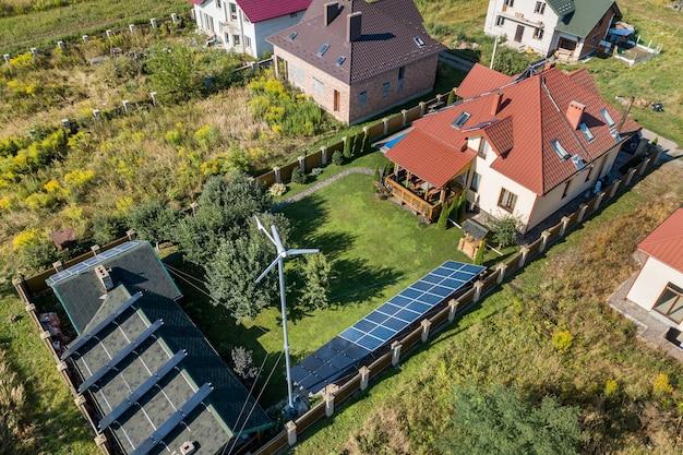 Vista aérea de una nueva casa autónoma con paneles solares, radiadores de calentamiento de agua en el techo y turbina eólica en patio verde.