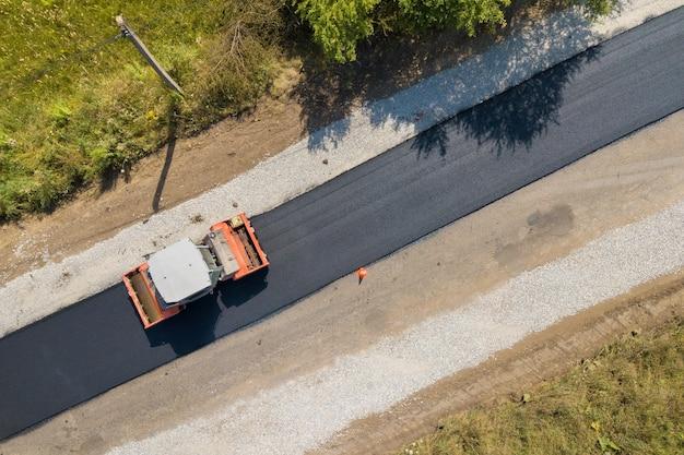 Vista aérea de la nueva construcción de carreteras con máquina de rodillos de vapor en el trabajo.