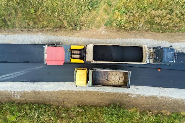 Vista aérea de la nueva construcción de carreteras con maquinaria de colocación de asfalto en el trabajo.
