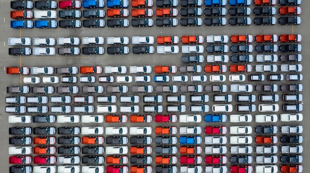 Vista aérea nueva terminal de exportación de automóviles, automóviles nuevos a la espera de importación y exportación en el puerto de aguas profundas.