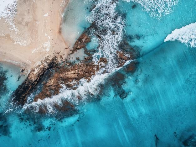 Vista aérea de olas, rocas y mar transparente