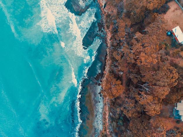 Vista aérea de las olas rompiendo en las rocas