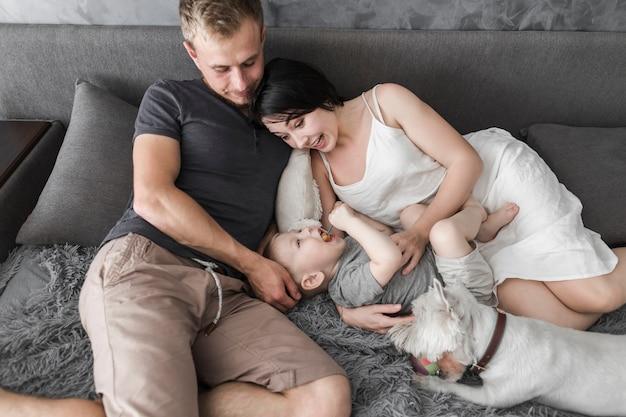 Una vista aérea de los padres divirtiéndose con su hijo y su perro en la cama