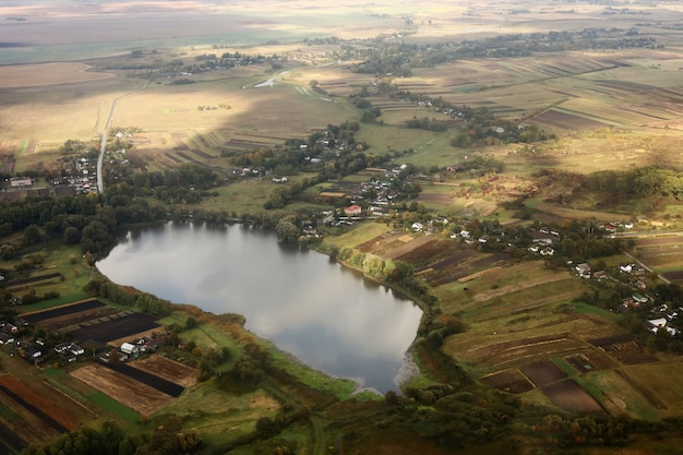 Vista aérea del paisaje del área de tierras de cultivo y el lago desde el avión. paisaje con lago.