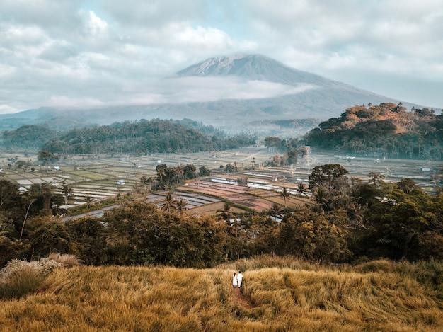 Vista aérea del paisaje pareja con terraza campo de arroz del volcán monte agung en bali en indonesia