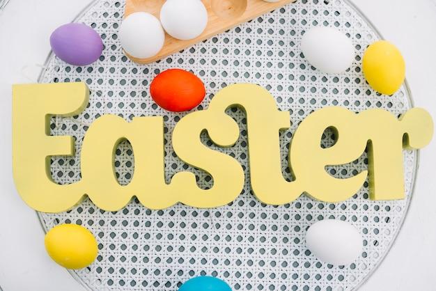 Una vista aérea de la palabra amarilla de pascua con huevos coloridos en mesa redonda blanca