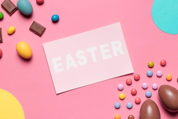 Una vista aérea de la palabra de pascua con los huevos de pascua del chocolate y los caramelos de la gema en fondo rosado