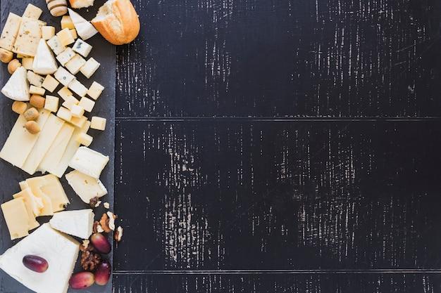 Una vista aérea de pan con diferentes tipos de queso con uvas sobre fondo negro con textura