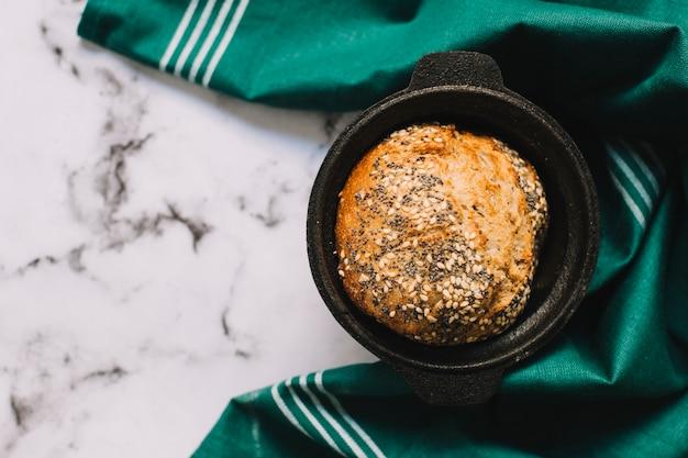 Una vista aérea de pan recién horneado en utensilio con servilleta verde sobre fondo de mármol