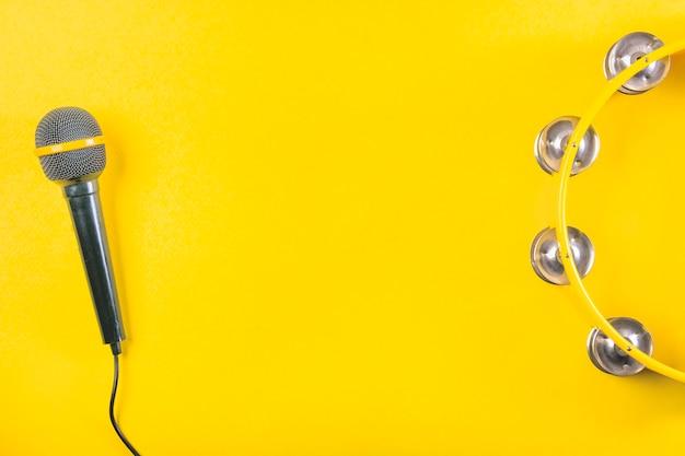 Vista aérea de pandereta con micrófono sobre fondo amarillo