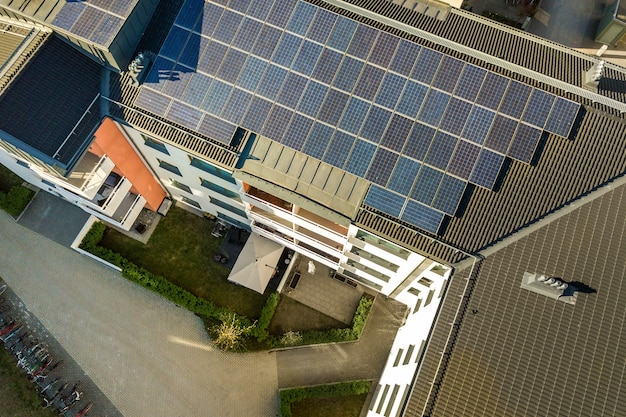 Vista aérea de paneles solares fotovoltaicos en la azotea de un bloque de construcción residencial para producir energía eléctrica limpia. concepto de vivienda autónoma.