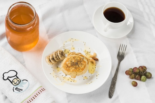 Una vista aérea de panqueques con miel; rodajas de banana y semillas de chia en un plato