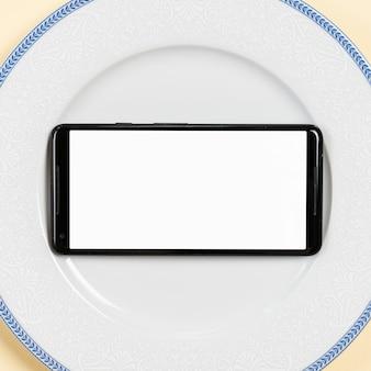 Una vista aérea de la pantalla en blanco móvil en plato blanco
