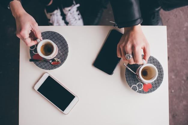 Vista aérea pareja jóvenes adultos tomando café con teléfono