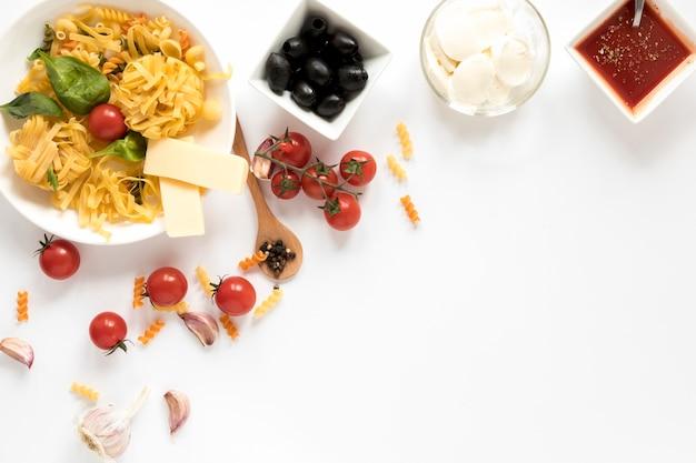 Vista aérea de pasta cruda y sus ingredientes aislados sobre superficie blanca