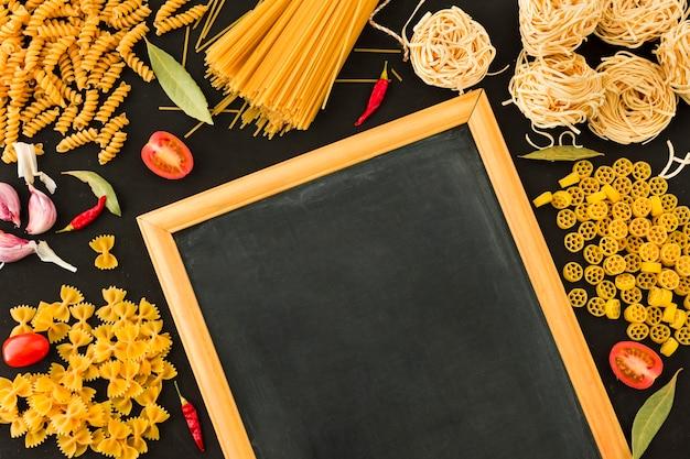 Una vista aérea de pastas crudas e ingredientes con pizarra pequeña en blanco