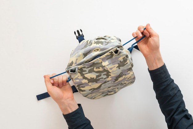 Una vista aérea de la persona que empaca las cosas en la bolsa antes de comenzar el viaje.