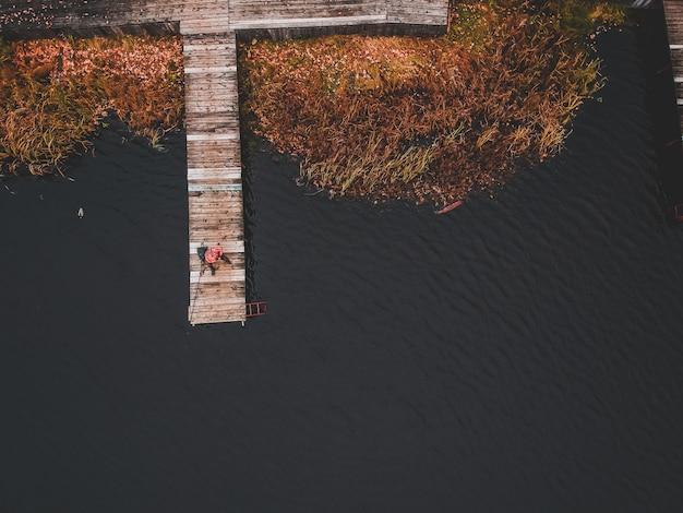 Vista aérea de un pescador con una caña de pescar en el muelle, orilla del lago, bosque de otoño. finlandia.