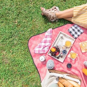 Vista aérea de la pierna de la mujer con desayuno en picnic sobre la hierba verde