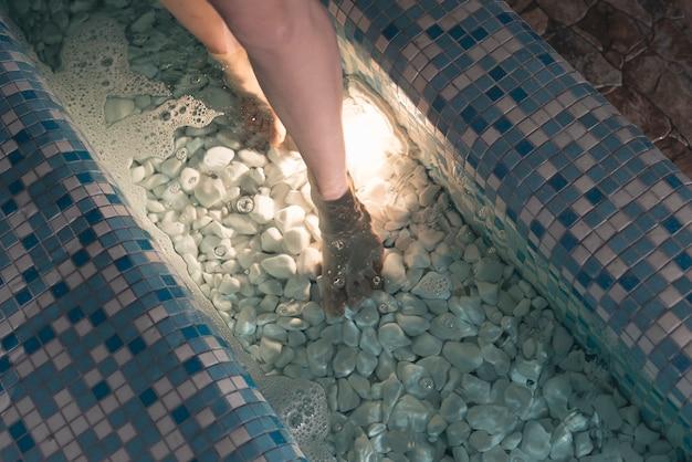 Vista aérea de los pies de la mujer en la bañera