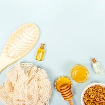 Vista aérea del pincel; botella de aceite esencial; tarro de miel polen de abeja y esponja vegetal