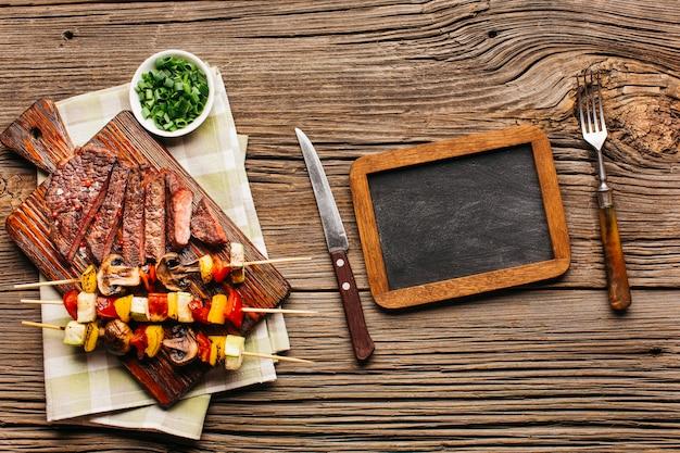 Vista aérea de un pincho de carne y bistec a la parrilla con pizarra en blanco