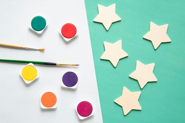 Vista aérea de pinturas de acuarela; forma de pincel y estrella en doble fondo colorido
