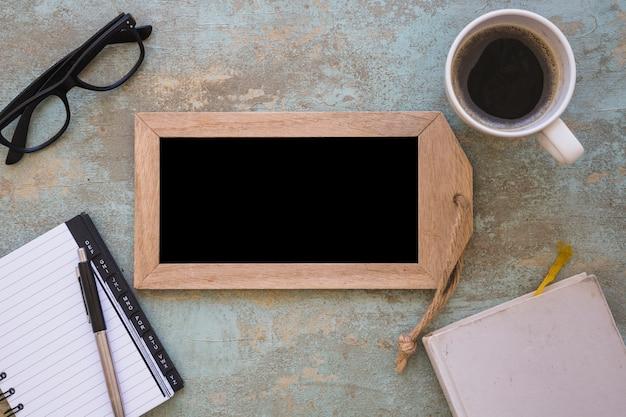 Una vista aérea de pizarra de madera; café y papelería sobre un fondo de grunge viejo