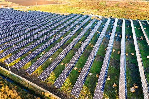 Vista aérea de la planta de energía solar en construcción en campo verde. montaje de cuadros eléctricos para la producción de energía ecológica limpia.