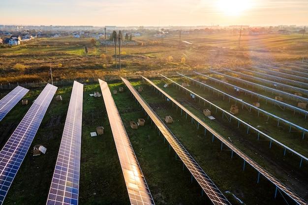 Vista aérea de la planta de energía solar en construcción en campo verde. montaje de cuadros eléctricos para producción de energía limpia y ecológica.